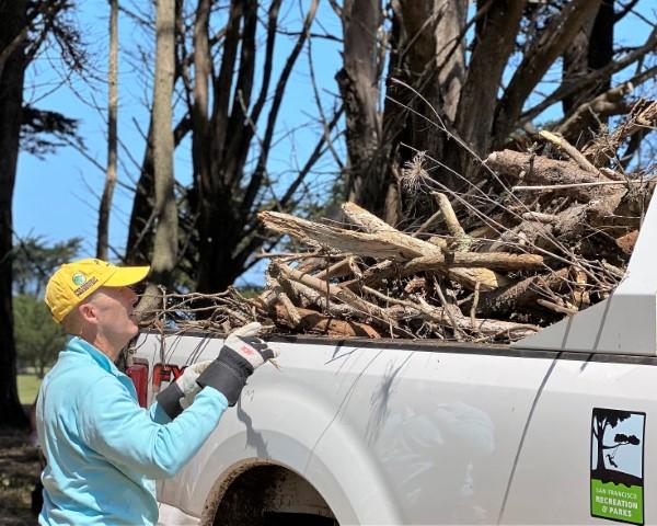 Volunteer load debris at Sharp Park
